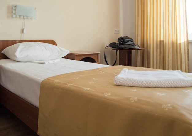 Hotel single room with a bed, an armchair and a table with men's black bags.