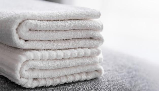 호텔 직원, 침대에 깨끗한 흰색 목욕 타월. 객실 청소 서비스.