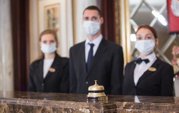 The hotel staff serves guests in medical masks