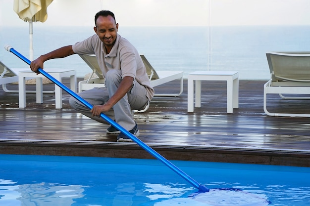 Hotel staff worker cleaning the pool