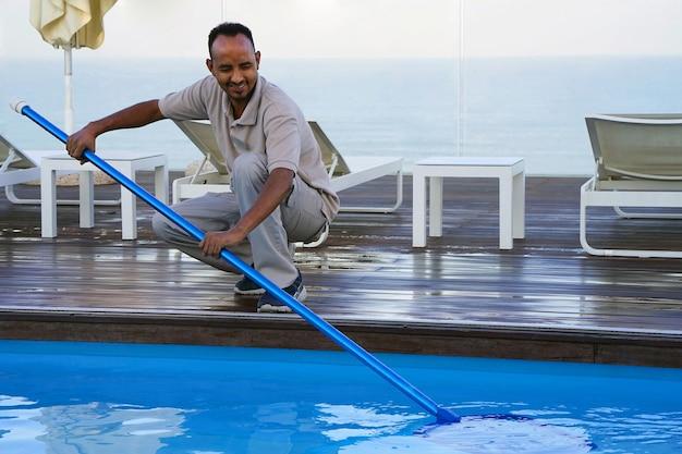 Работник отеля чистит бассейн