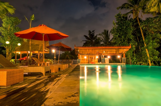 Hotel in the tropical jungle. night swimming pool. palms, umbrellas, sunbeds and bar. nobody