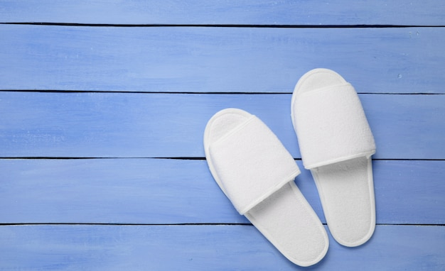 Hotel white slippers on a blue wooden floor.