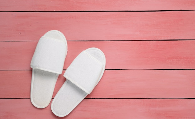 Hotel white slippers on red wooden floor.