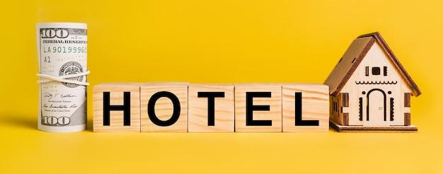 노란색 배경에 집 미니어처 모델과 돈이 있는 호텔. 비즈니스, 금융, 신용, 세금, 부동산, 가정, 주택의 개념