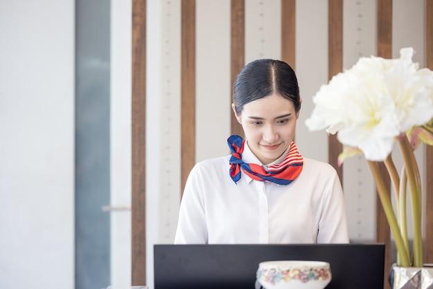 カウンターの後ろでプロの受付係として働くホテルの女性 Premium写真
