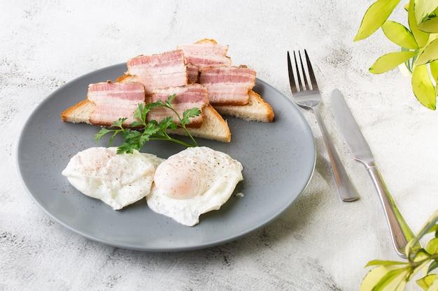 サワー種のトーストにベーコンとポーチドエッグ。白い大理石の背景に分離されました。手作りの料理。おいしい朝食。セレクティブフォーカス。 hotizontalの写真。