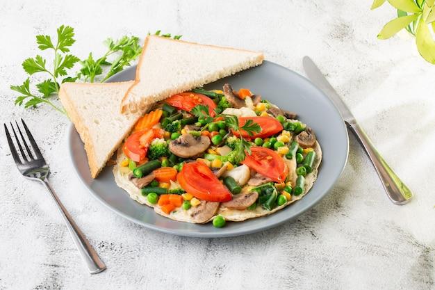 白い大理石の背景に分離された野菜、トマト、マッシュルーム、インゲン、エンドウ豆、トウモロコシ、サワー種のトーストとオムレツ。手作りの料理。おいしい朝食。セレクティブフォーカス。 hotizontalの写真。
