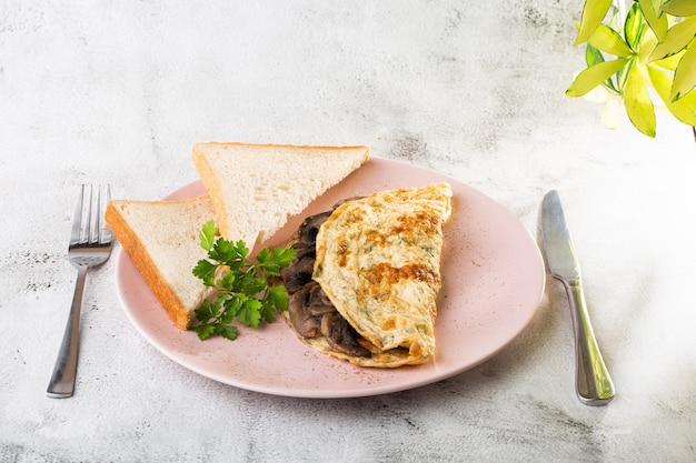 キノコとサワー種のトーストが白い大理石の背景に分離されたオムレツ。手作りの料理。おいしい朝食。セレクティブフォーカス。 hotizontalの写真。