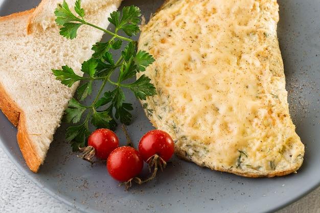 白い大理石の背景に分離されたチーズ、チェリートマト、サワー種のトーストとオムレツ。手作りの料理。おいしい朝食。セレクティブフォーカス。 hotizontalの写真。