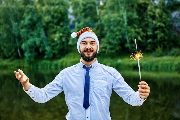 Houng smiling businessman, wearing a santa claus hat, holds a burning sparkler in his hand, standing against background of green trees and  river in wild.