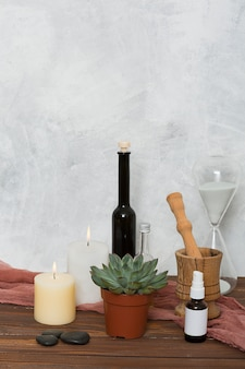 Hour glass; cactus plant; lighted candle; lastone; essential oil; wooden mortar and pastel on table against wall