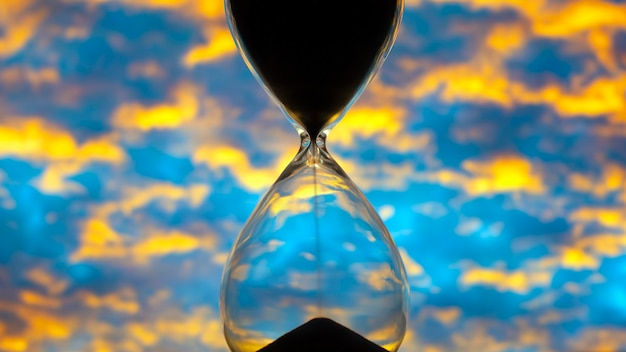 Hourglass against the sunset bright sky. time and implementation of plans