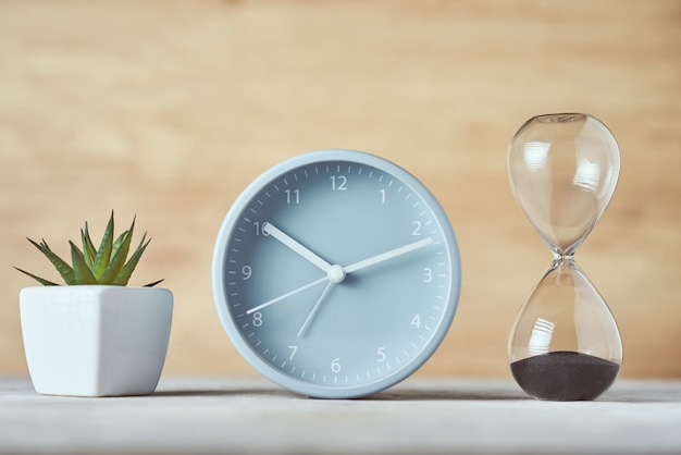 Hourglass, alarm clock and plant on table, close up