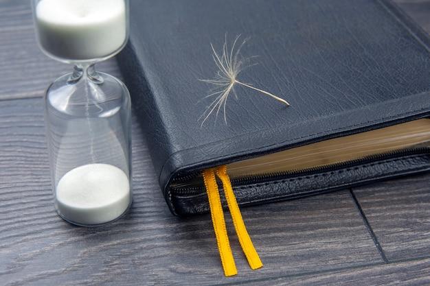 민들레 씨앗과 모래 시계와 성경. 하나님을 믿는 신앙의 씨를 뿌리십시오. 기독교와 종교