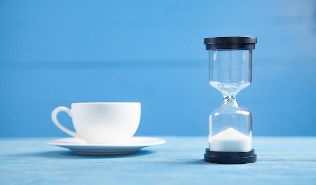«песочные часы» и кофейная чашка на синем фоне.