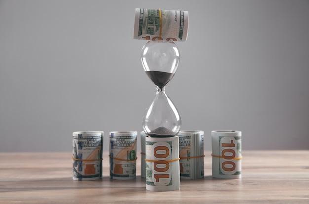 Песочные часы и деньги на столе. время - деньги