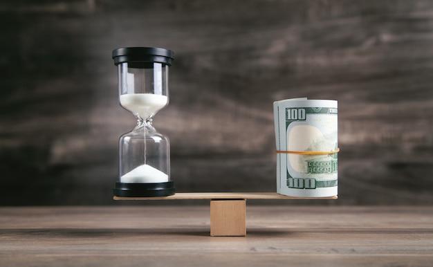 Песочные часы и деньги на деревянном балансе.