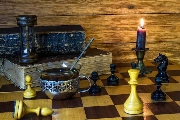 砂時計と古い本、チェスの駒、お茶のキャップ、燃えるろうそくがチェス盤の上に立っています。