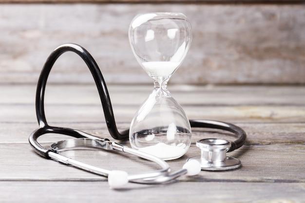 모래 시계와 청진기. 짧은 생활 개념.