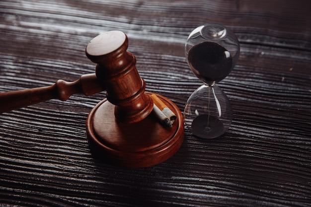 Песочные часы и деревянный молоток судьи на столе