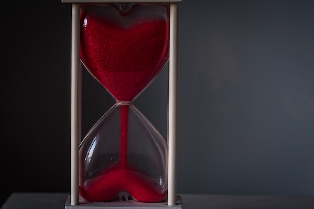 Hourglass as love concept for valentines day on dark gray background.