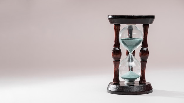 Hourglass as time passing concept for business deadline on colored background