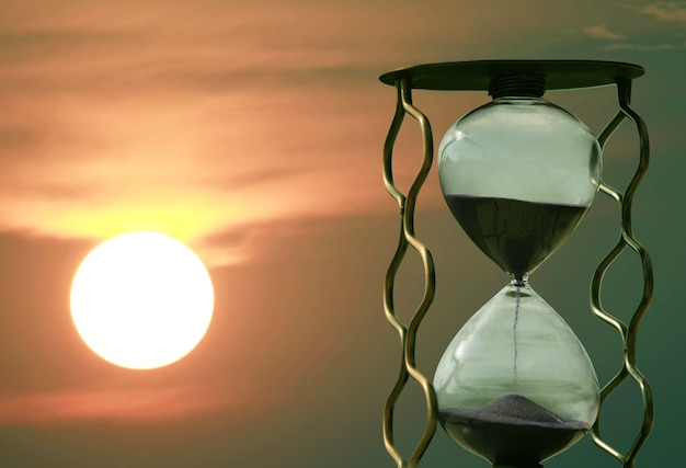 Hourglass on the background of a sunset. fast passing of time