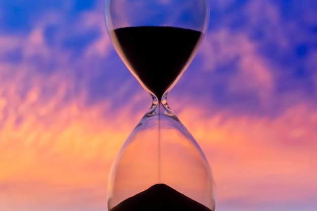 Hourglass on the background of a sunset sky. the value of time in life. an eternity.