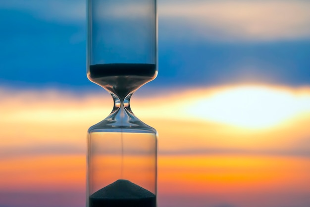 Hourglass on the background of a sunset.