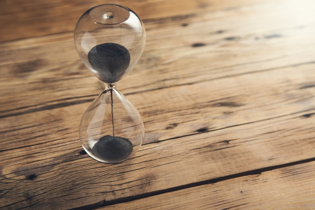 Hourglass on the brown wooden table