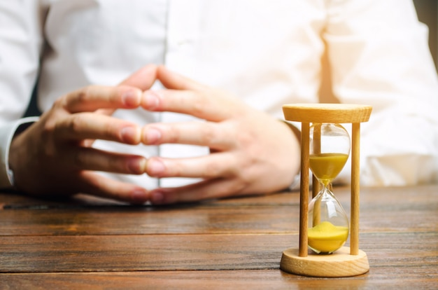 An hourglass and businessman holds his hands