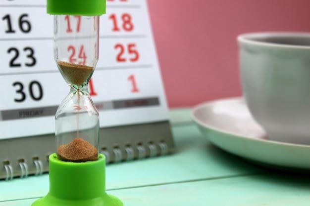 デスクトップに砂時計のお茶が立っています。取り返しのつかないほど離れていく時間の象徴であり、ビジネスを思い起こさせます。