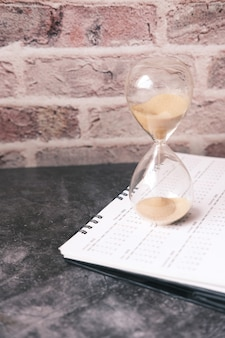 Hourglass on a calendar and flowing through the bulb of sandglass