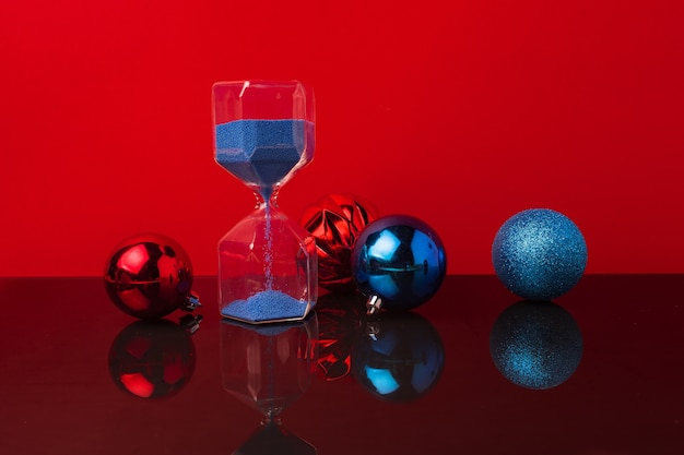 Hourglass and christmas balls against red