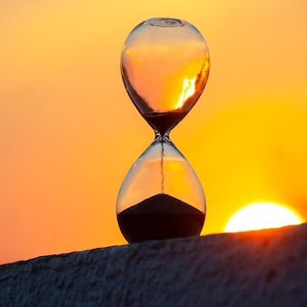 Hourglass counts the length of time against the background of the evening sun