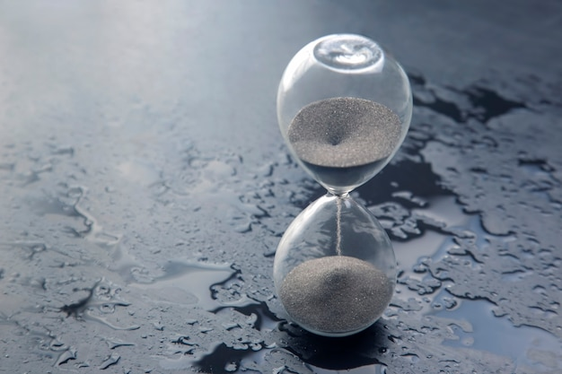 Hourglass on a dark background. time is money. business solutions in time.