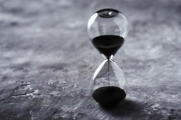 Hourglass on dark background with copy space. concept of running out of time and deadline