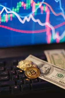 차트 배경에 있는 컴퓨터 키보드의 모래시계, 달러, 비트코인