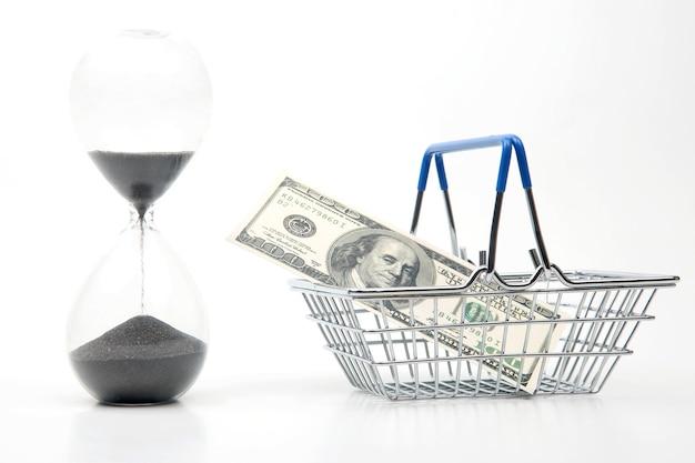 모래 시계, 달러 및 흰색 배경에 시장 식료품 쇼핑 카트