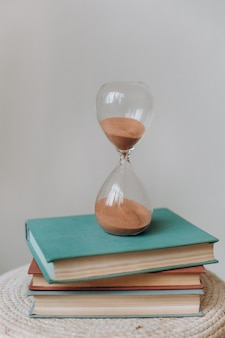 Hourglass flask retro stand stack of books measuring time countdown