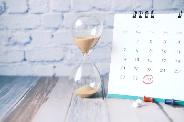 Hourglass flowing through the bulb of sandglass and calendar on table