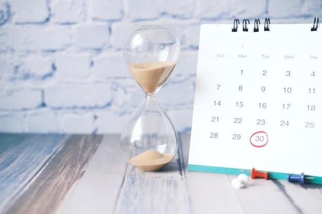 Песочные часы, протекающие через лампочку песочных часов и календаря на столе