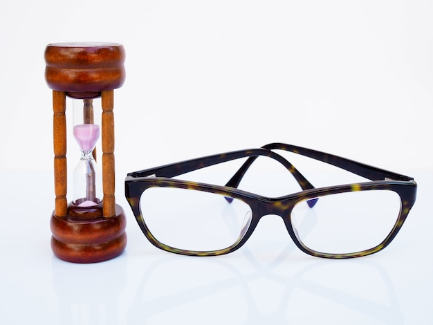 Hourglass and glasses isolated on white surface, count down of timing to take care of health of eyes, limited time concept.