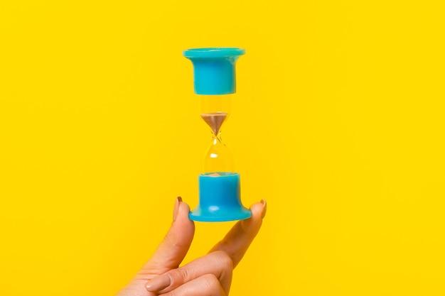 Песочные часы в руке над желтым Premium Фотографии
