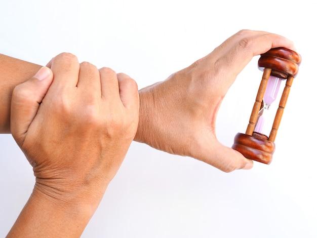 손에 모래 시계, 건강 관리 및 운동, 팔, 뼈와 근육 손목 통증, 흰색 표면에 고립 된 시간.