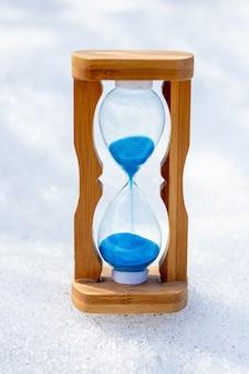 Песочные часы на снегу в солнечную погоду. зимнее время