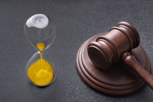 Hourglass and judges gavel on black. law and time.