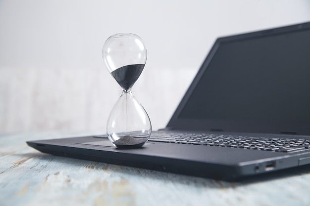 Hourglass and laptop on the desk. time. business