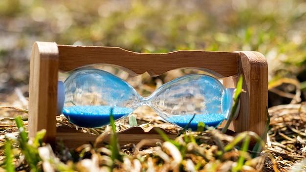 砂時計は草の上にあります。時間停止のコンセプト